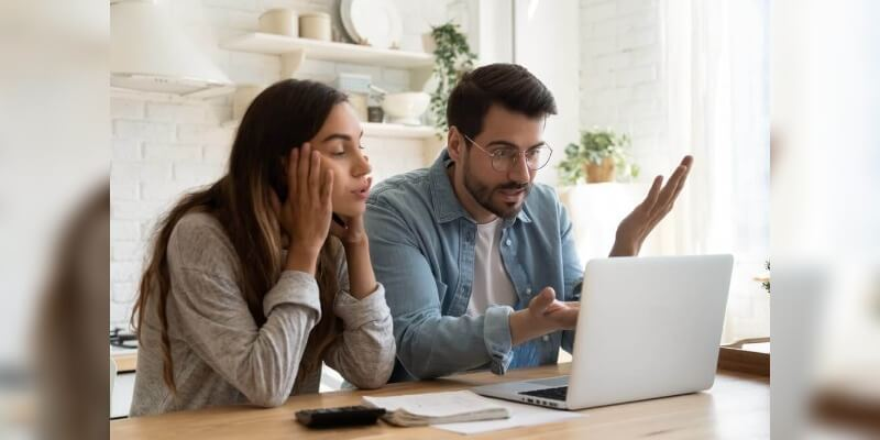 Mortgage down valuations - what to do next? Image of a couple starting at computer screen with frustration.