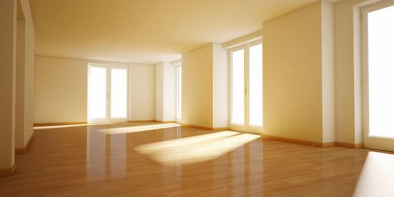 Owning/Selling an empty house. Image of a bare property with sun coming through the windows.