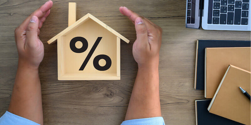 Yes Homebuyers - How much do we offer? Image of a house with a percentage sign on a desk.