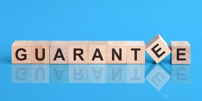 Yes Homebuyers - Offer Guarantee so you know price will not change. Image of the word Guarantee spelt with wooden blocks.