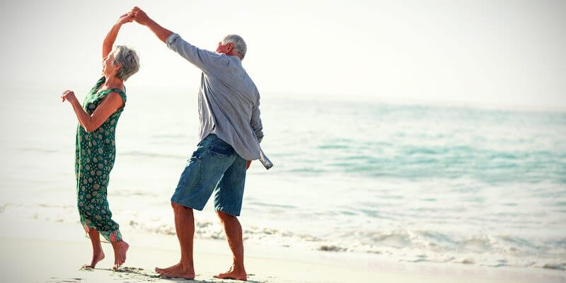 Sell house for Retirement or Downsizing - Yes Homebuyers. Image of a retiring couple dancing on the beach