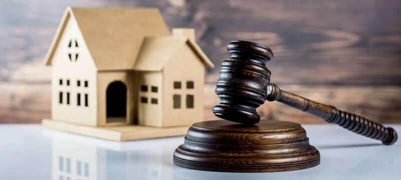 Image of a gavel in front of a property