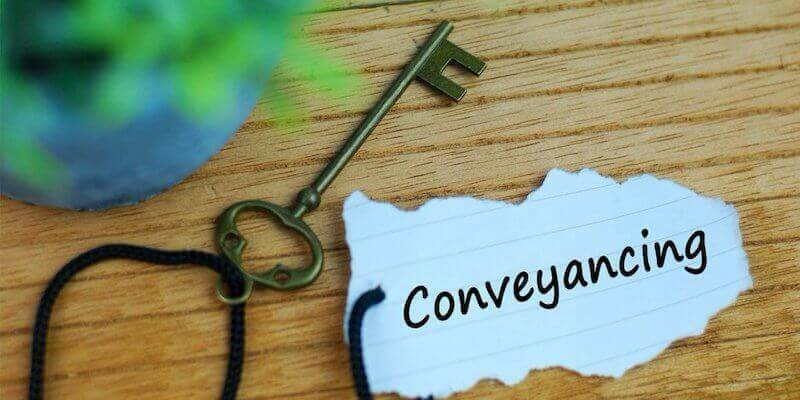 """What is conveyancing? Image of a house key with a """"Conveyancing"""" tag on it."""