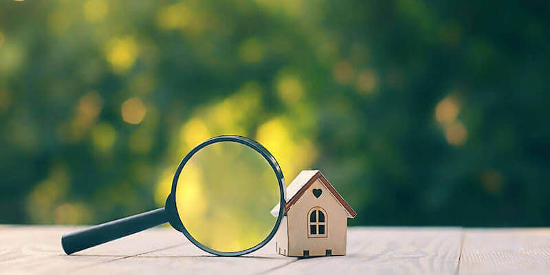 Image of a magnifying glass against a model house