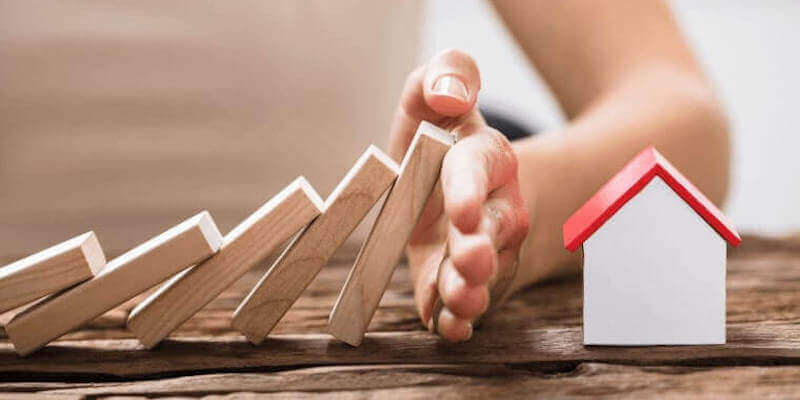 A hand stopping falling dominos before falling onto a house - what to do when your house sale falls through
