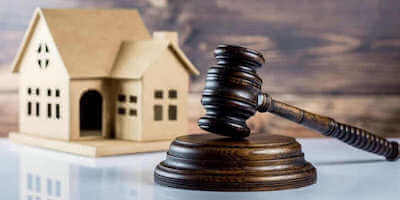 Is auctioning your house a good idea? Image of a gavel in front of a model house