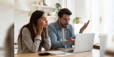 Frustrated man and woman receive down valuation and research what to do next