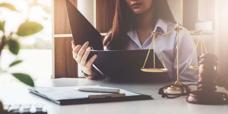 Woman in law office sorting Lasting Power Of Attorney or Probate to sell a property