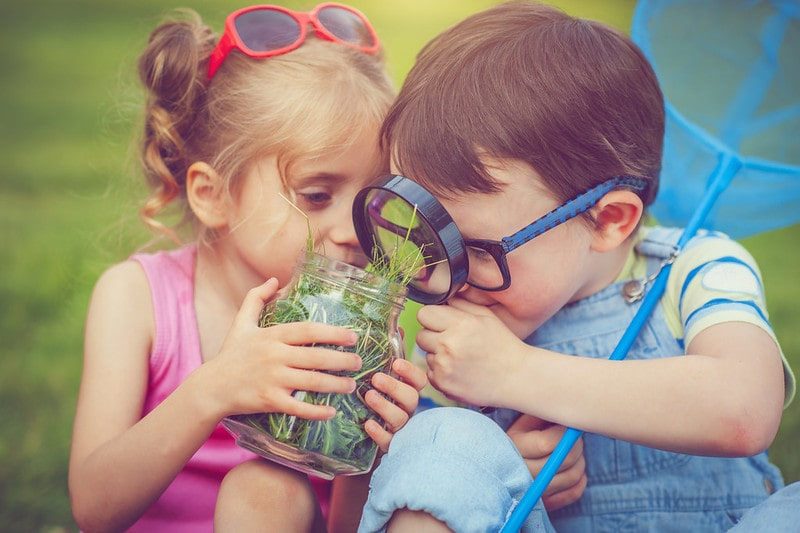 Two small children looking at a jar full of grass through a magnifying glass