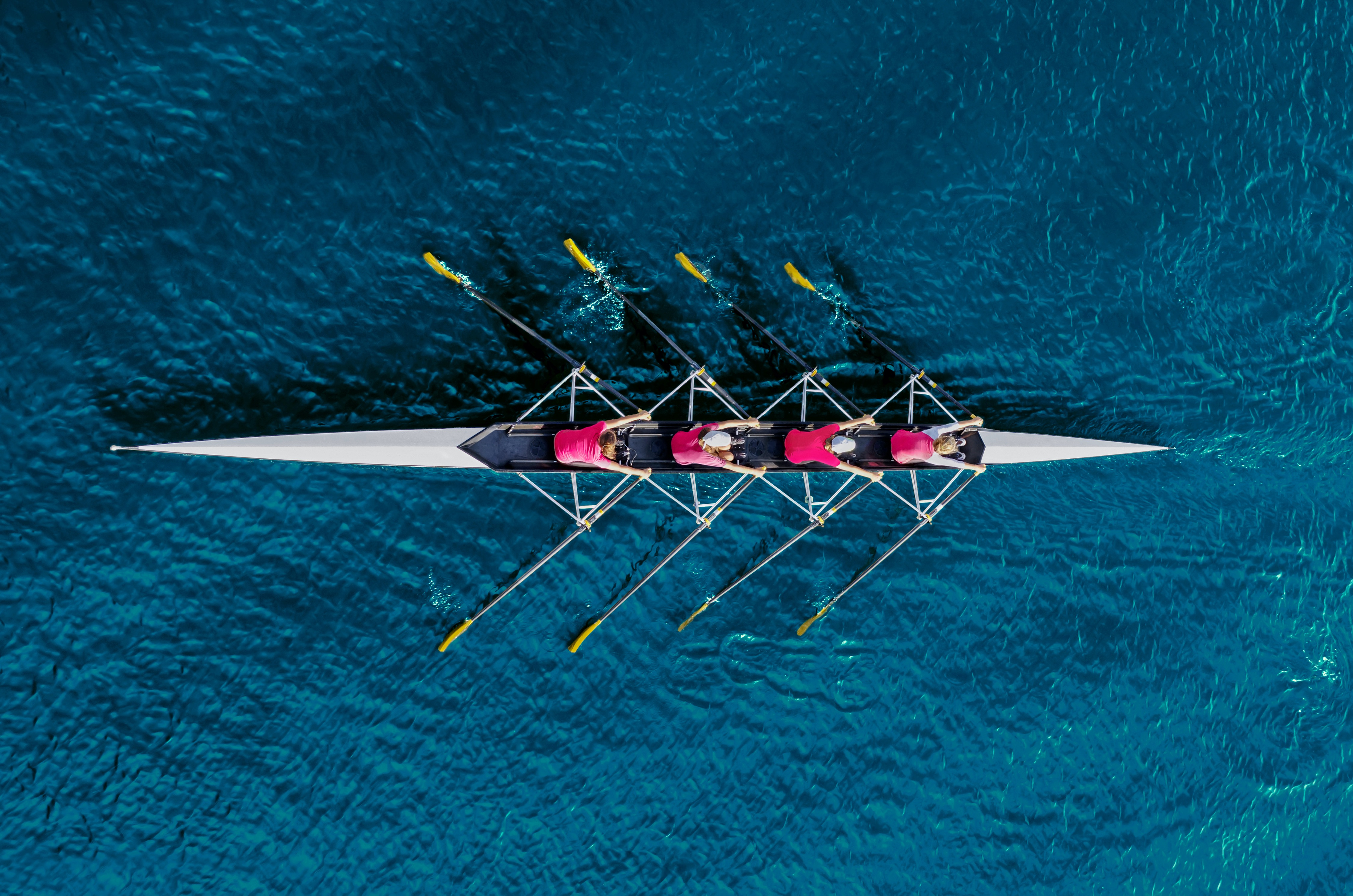 A team of four rowers, rowing together in blue water.