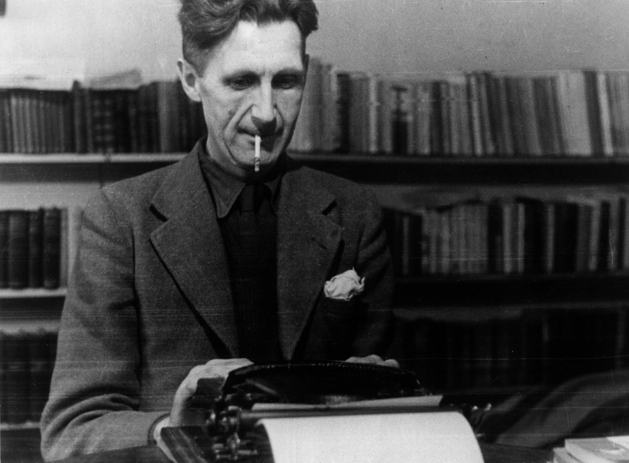 George Orwell sitting at his typewriter with a cigarette in his mouth