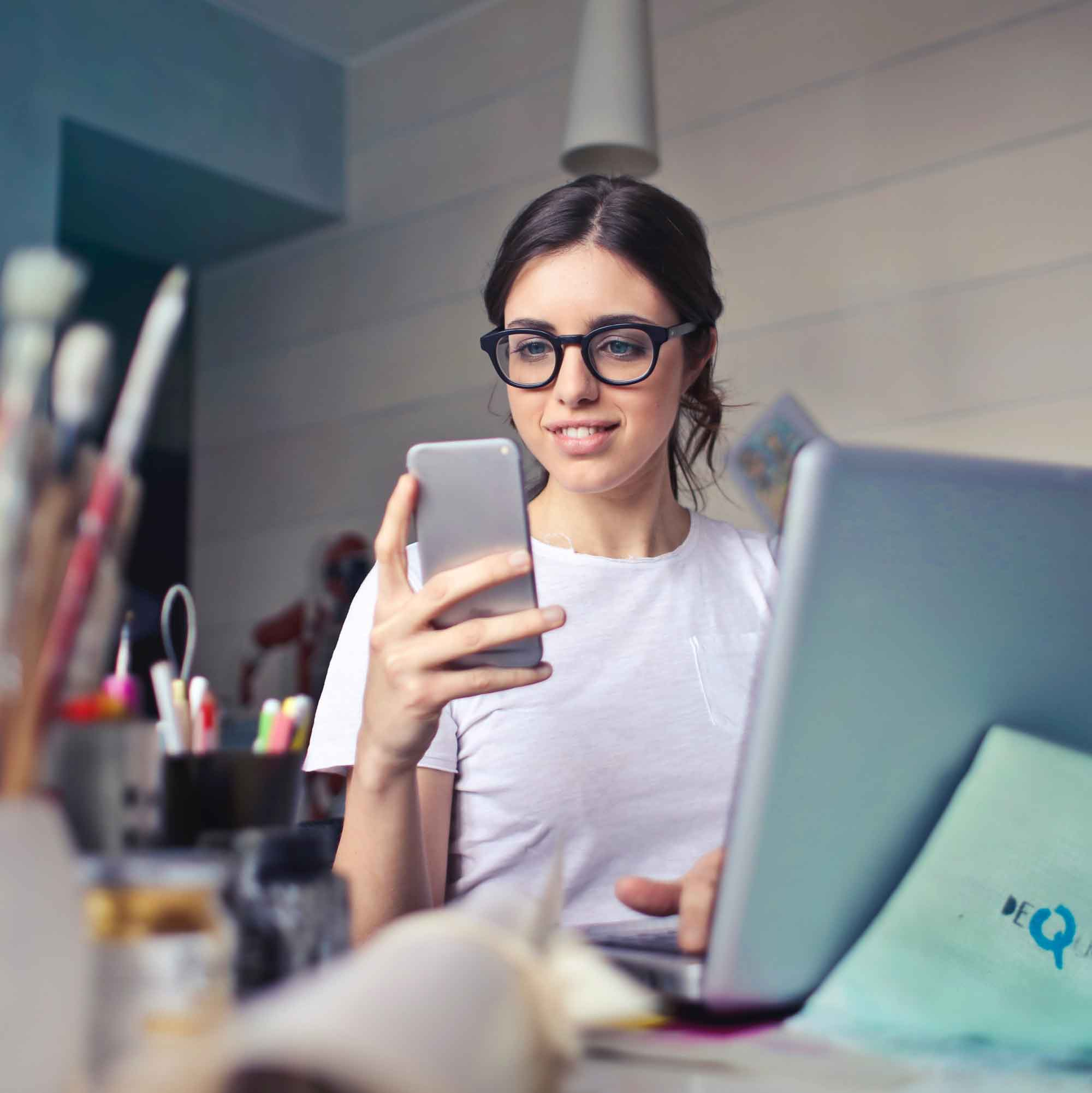 Woman sat at desk reading a guide to small business websites on her phone