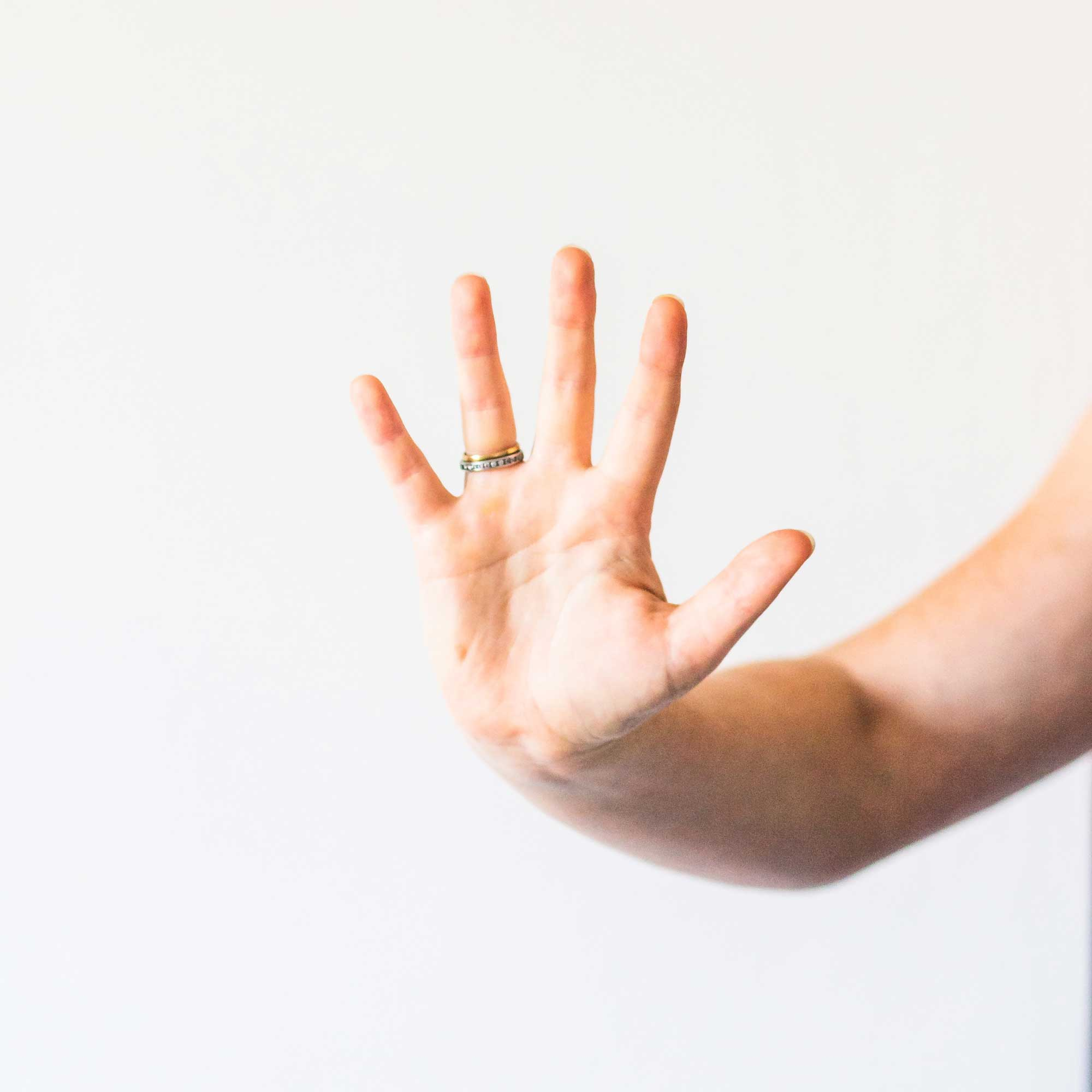 Person's palm with 5 fingers showing against white background