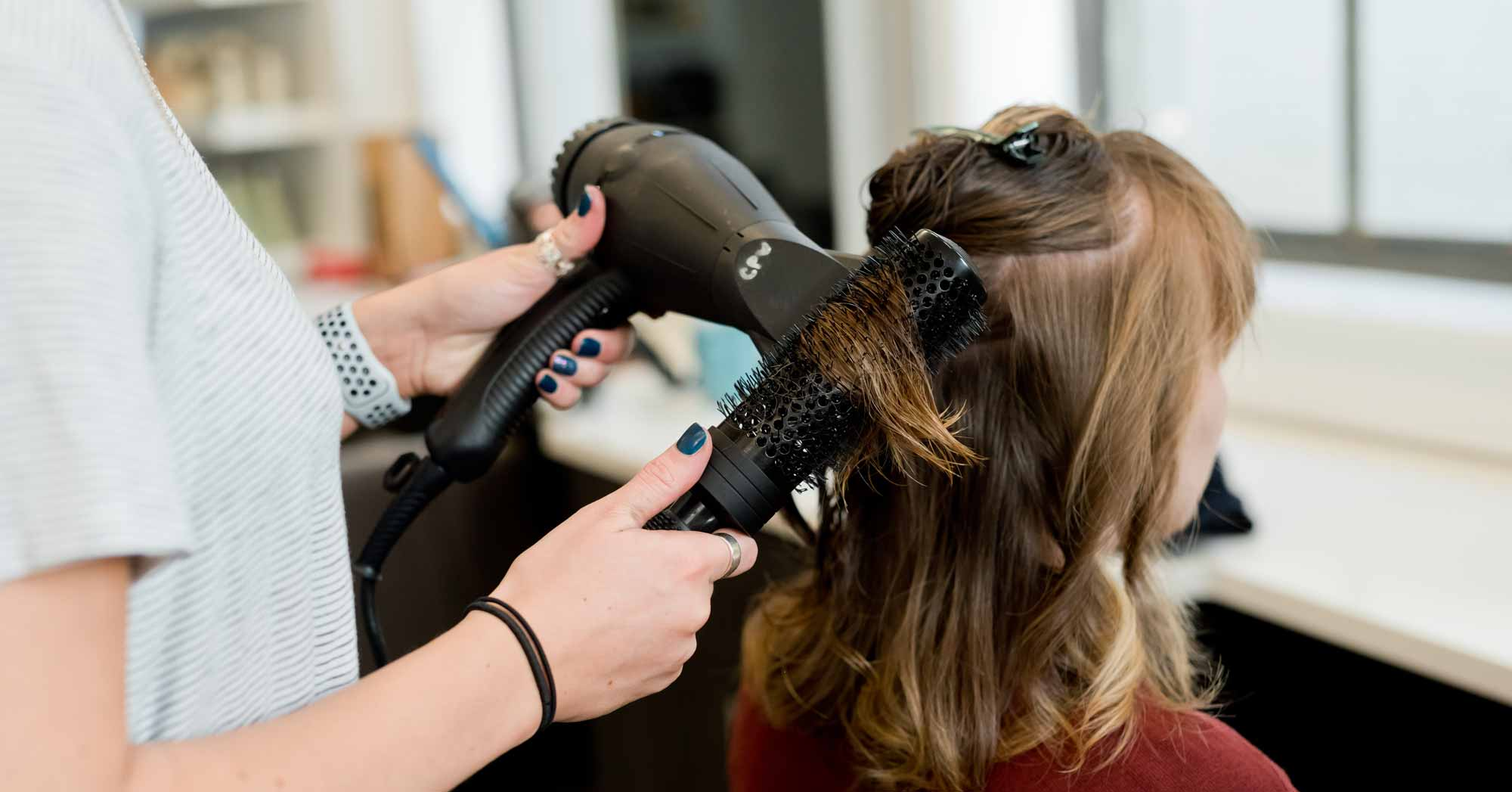 Woman blow drying hair in hairdressers