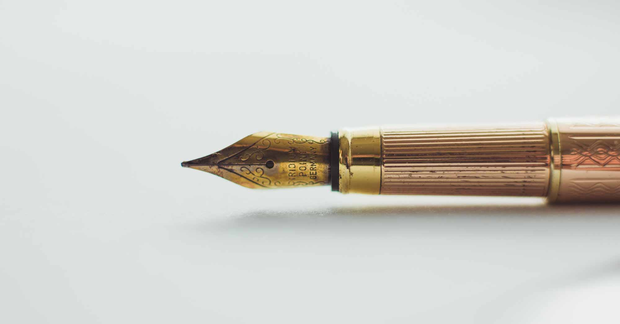 Gold fountain pen laying on its side