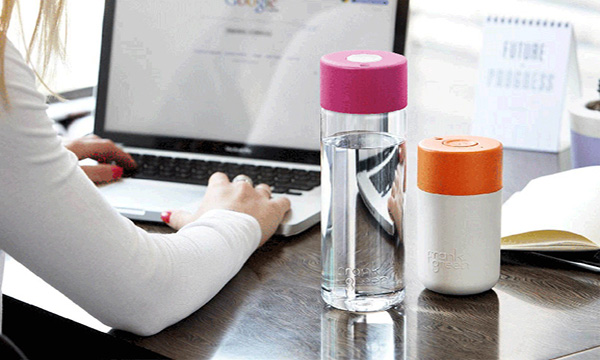 image of woman working on laptop with water bottles next to her.
