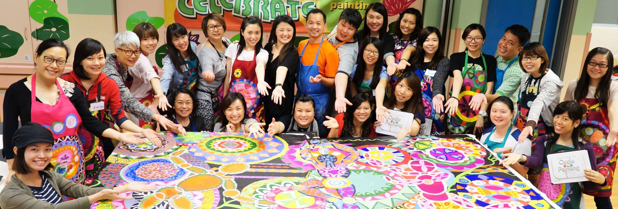 group of people smiling next to their painting after participating in a collaborative art class
