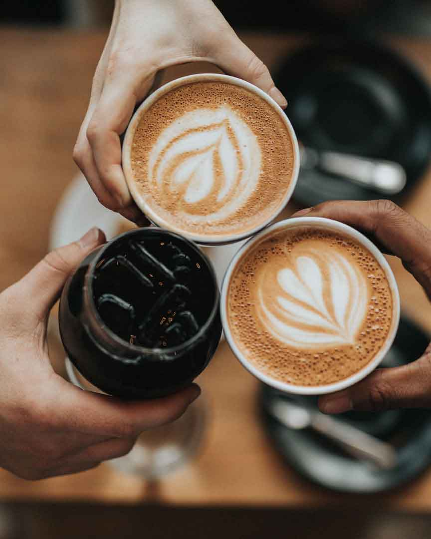 Tre venner der drikker kaffe sammen