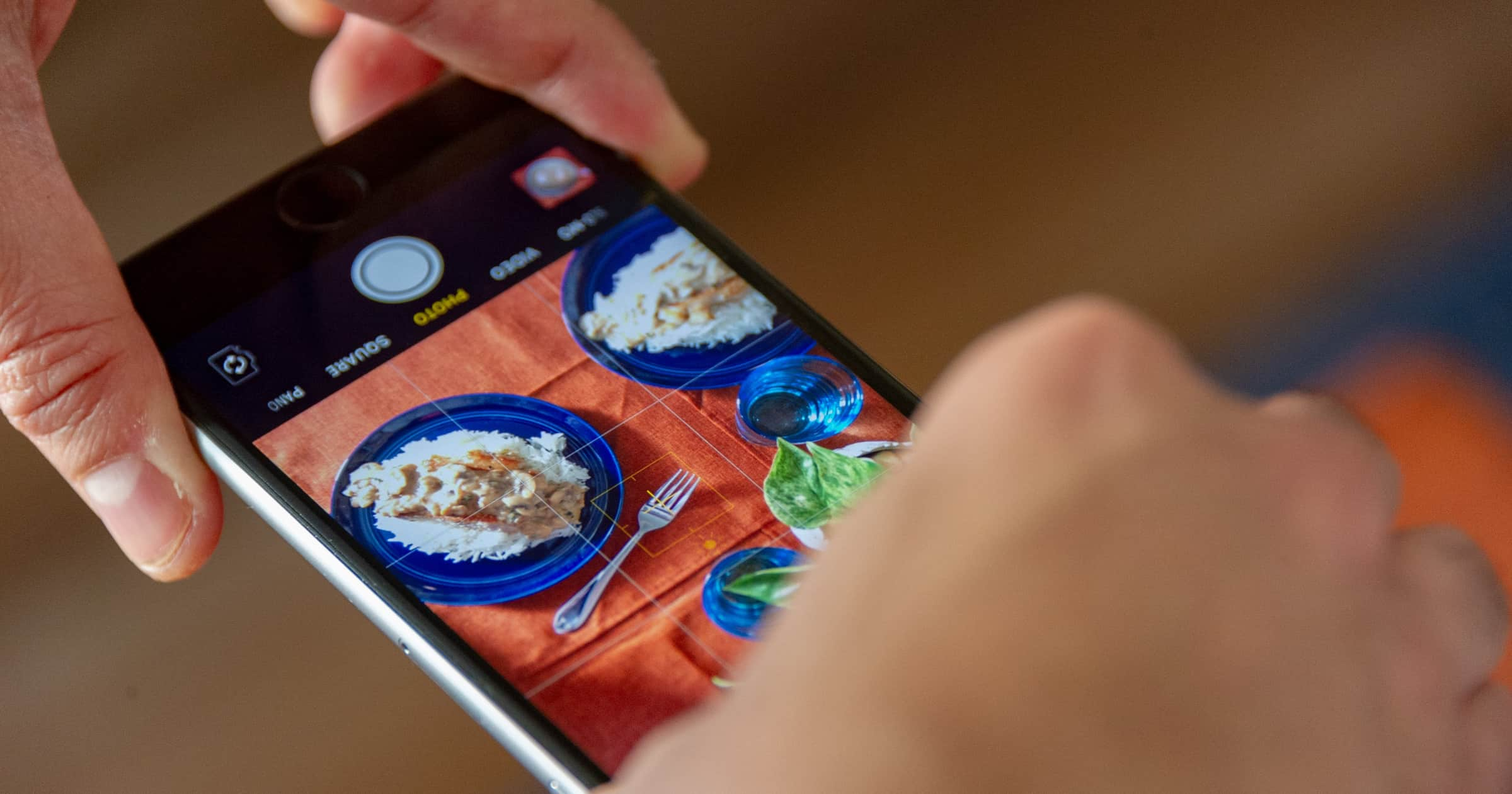 a person taking a photo of food before they use one of the essential design apps to edit it