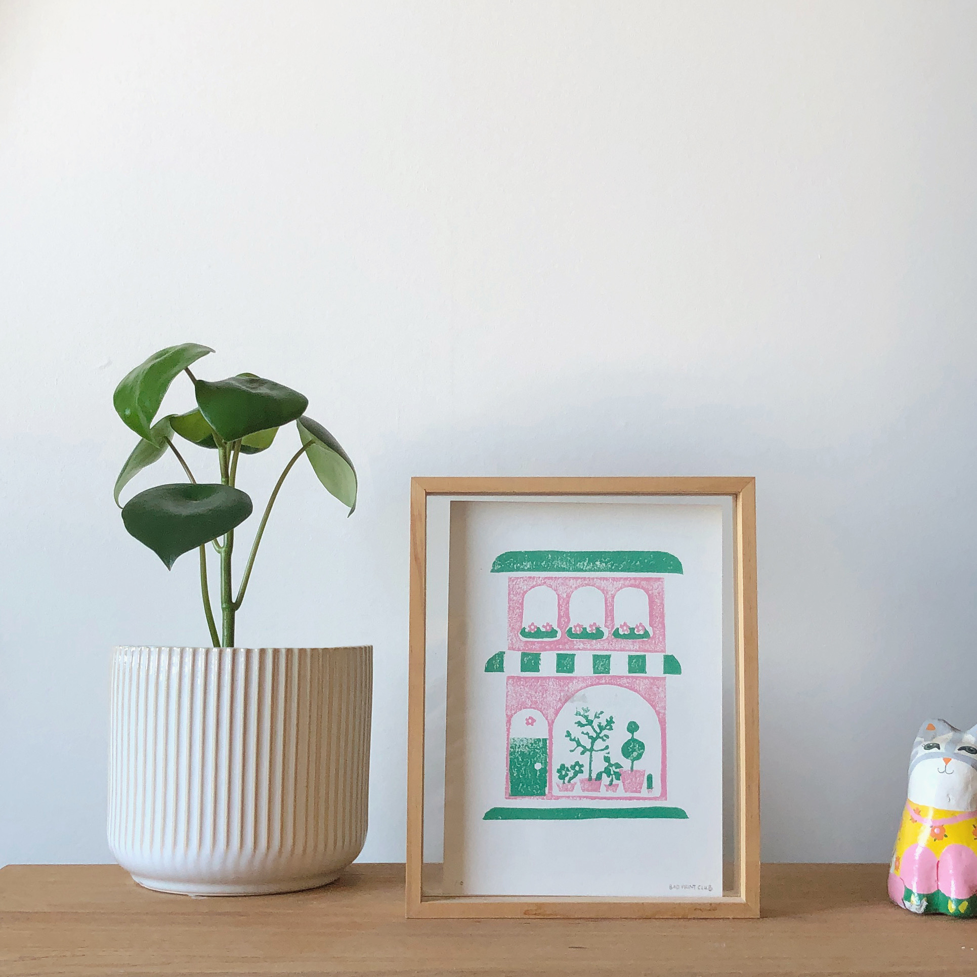 Pot plant next to a framed print of a pink and green shop front.