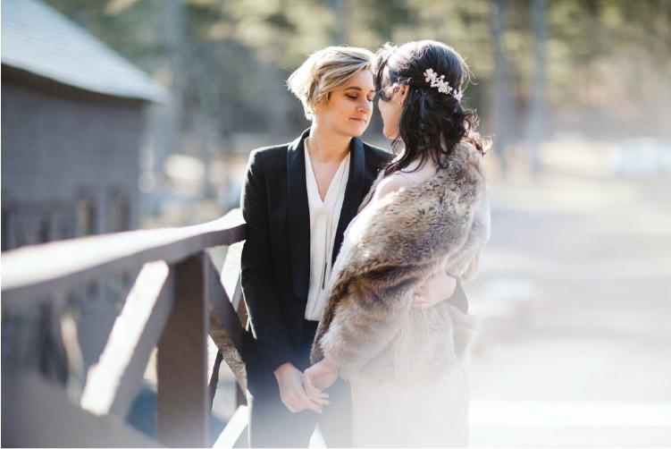 Two brides holding hands on a rustic bridge.