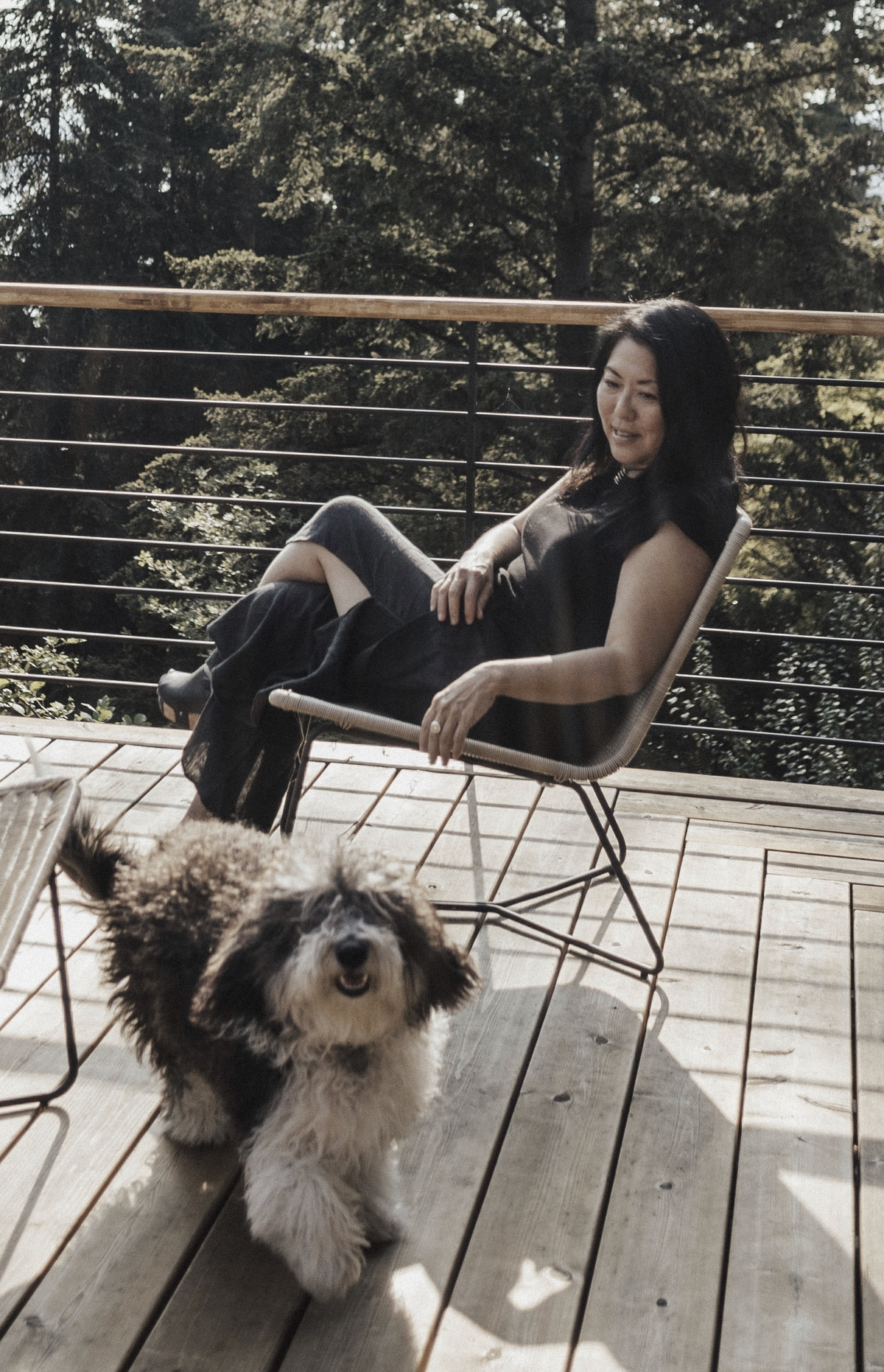 Kelly sitting on her deck reaching casually for her furry black and white dog who is running towards the camera.