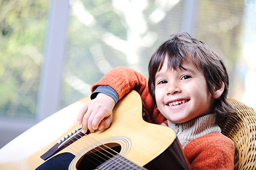Miguel learns guitar at Greenwich Arts Academy