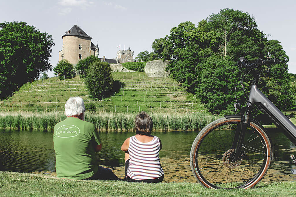 Man en vrouw zittend aan een meer, met uitzicht op burcht