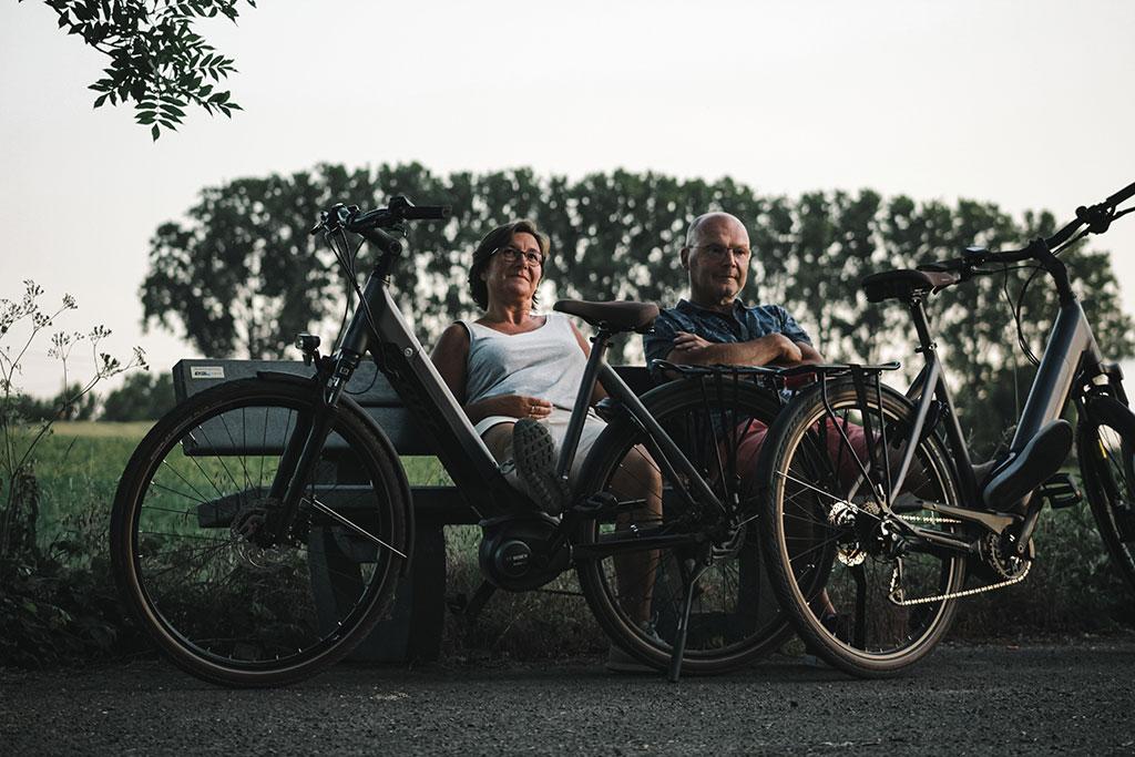Man en vrouw rusten op een bank met e bikes op de voorgrond