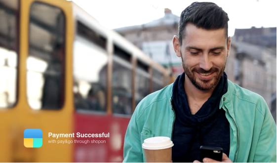 A midaged guy looking into his smartphone while holding a coffee