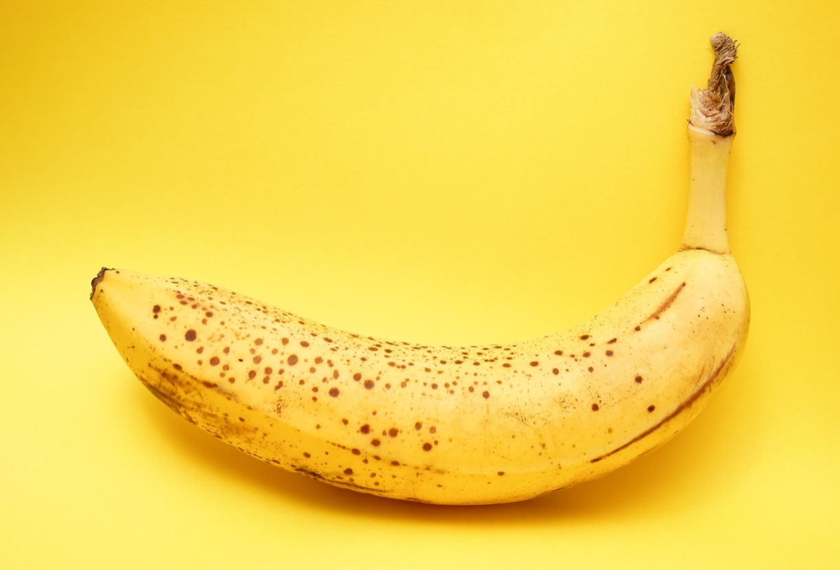 Image of banana with brown spots against a yellow background