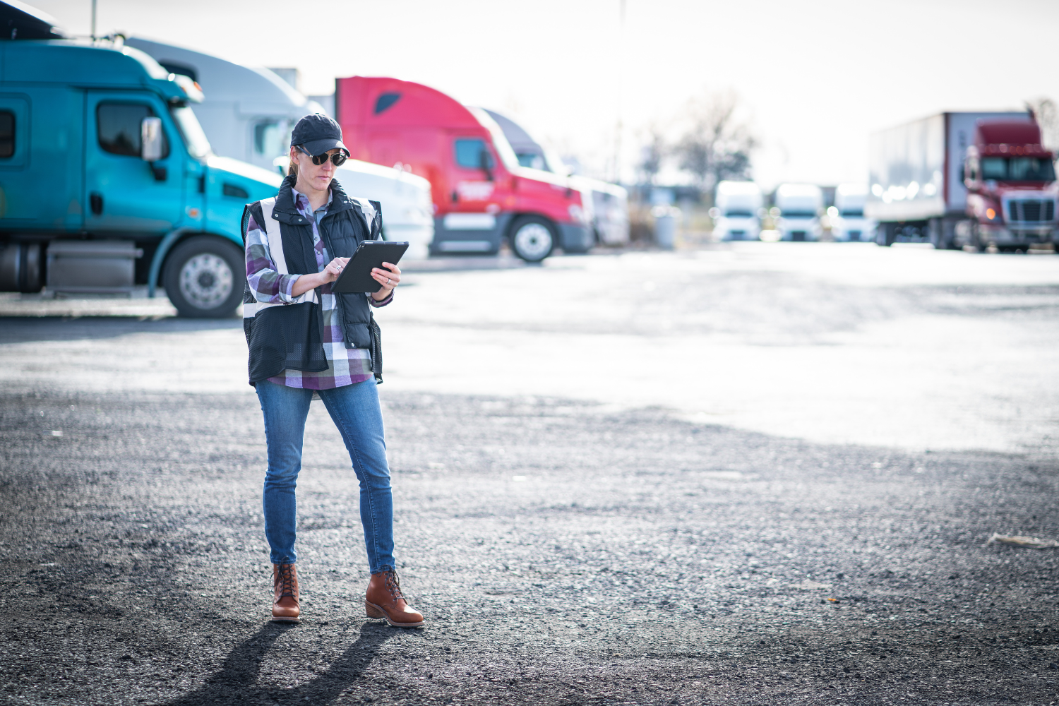An employee utilizing yard management software to control trucks moving trailers and inventory assets in and out of the operations yard