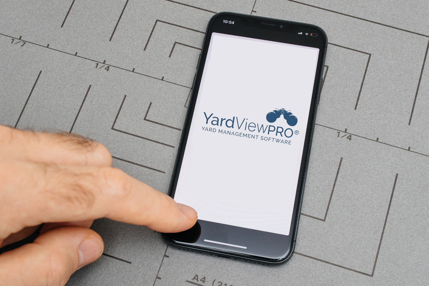 Image of a hand on a piece of paper designed like a target selecting a YMS system by touching a phone call button with the YardView Pro Yard Management Software logo on the screen