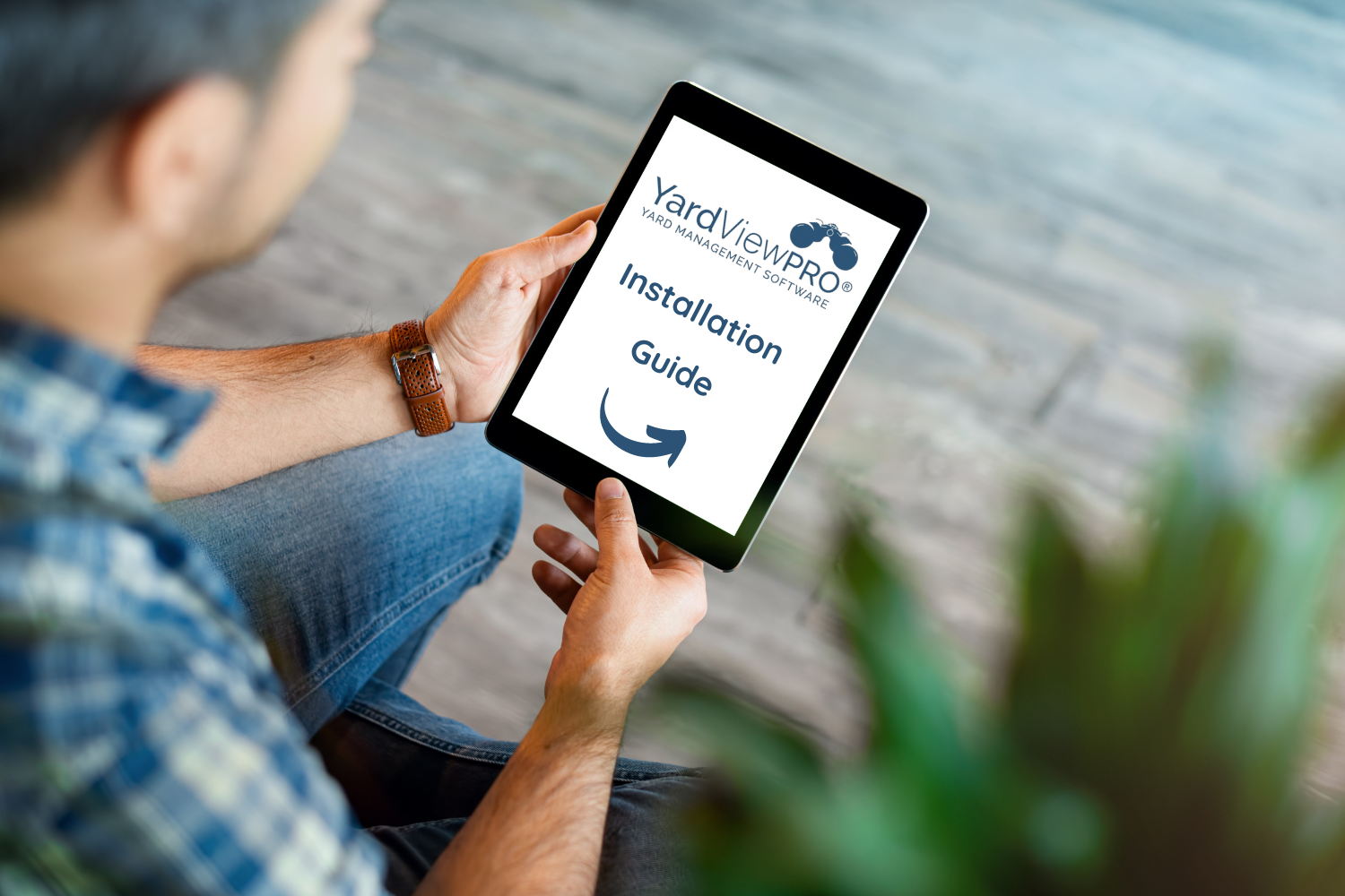 Man holding a tablet reading an e-document about a guide to installing YardView yard management software