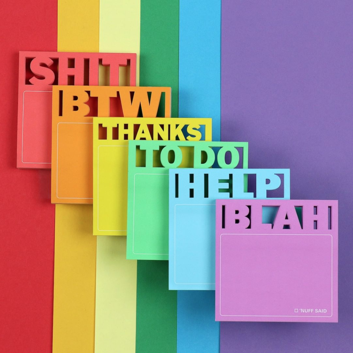 On a rainbow colored background the Die cut sticky notes are placed on top of each other.