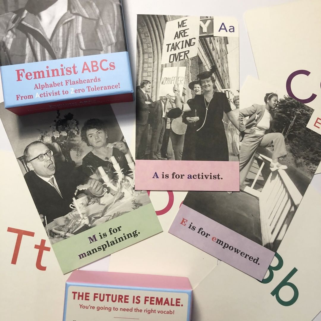 Feminist ABC cards are laid across the image. You can see the front packaging of the box in the corner with 3 cards with images.