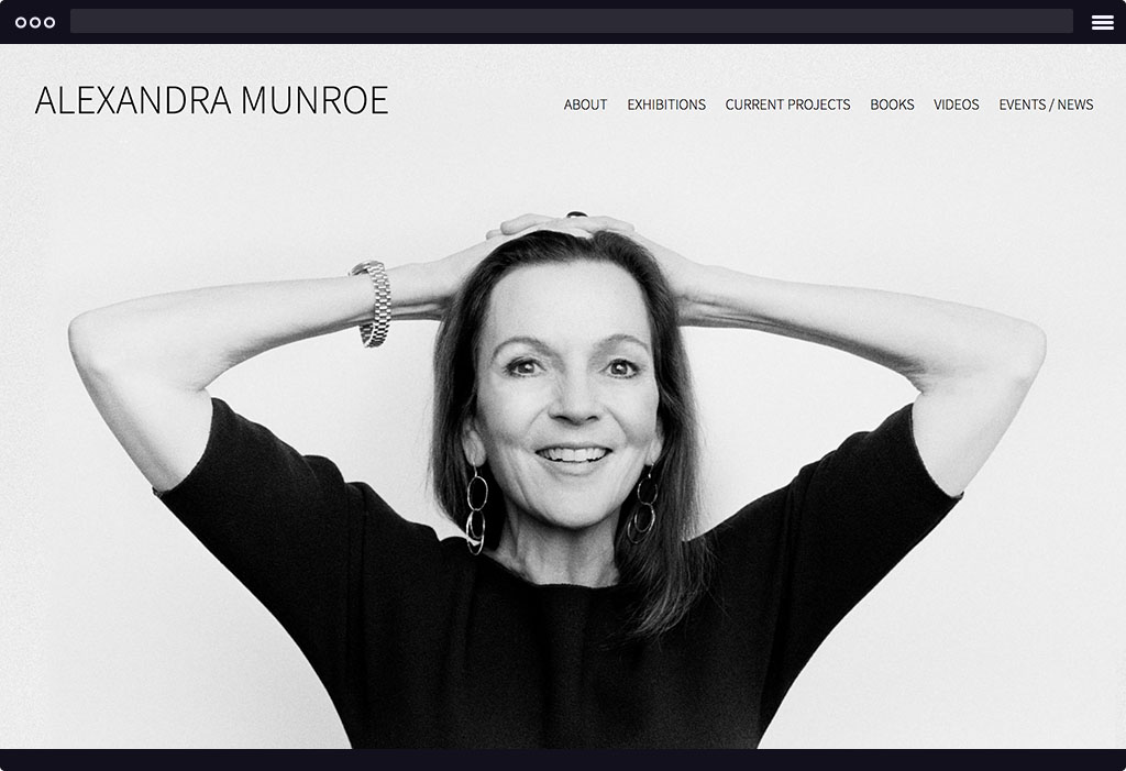 This is a screenshot of Alexandra Munroe's website homepage. The page features a large self portrait image of Munroe in black and white. Munroe is smiling broadly with her hands behind her head.