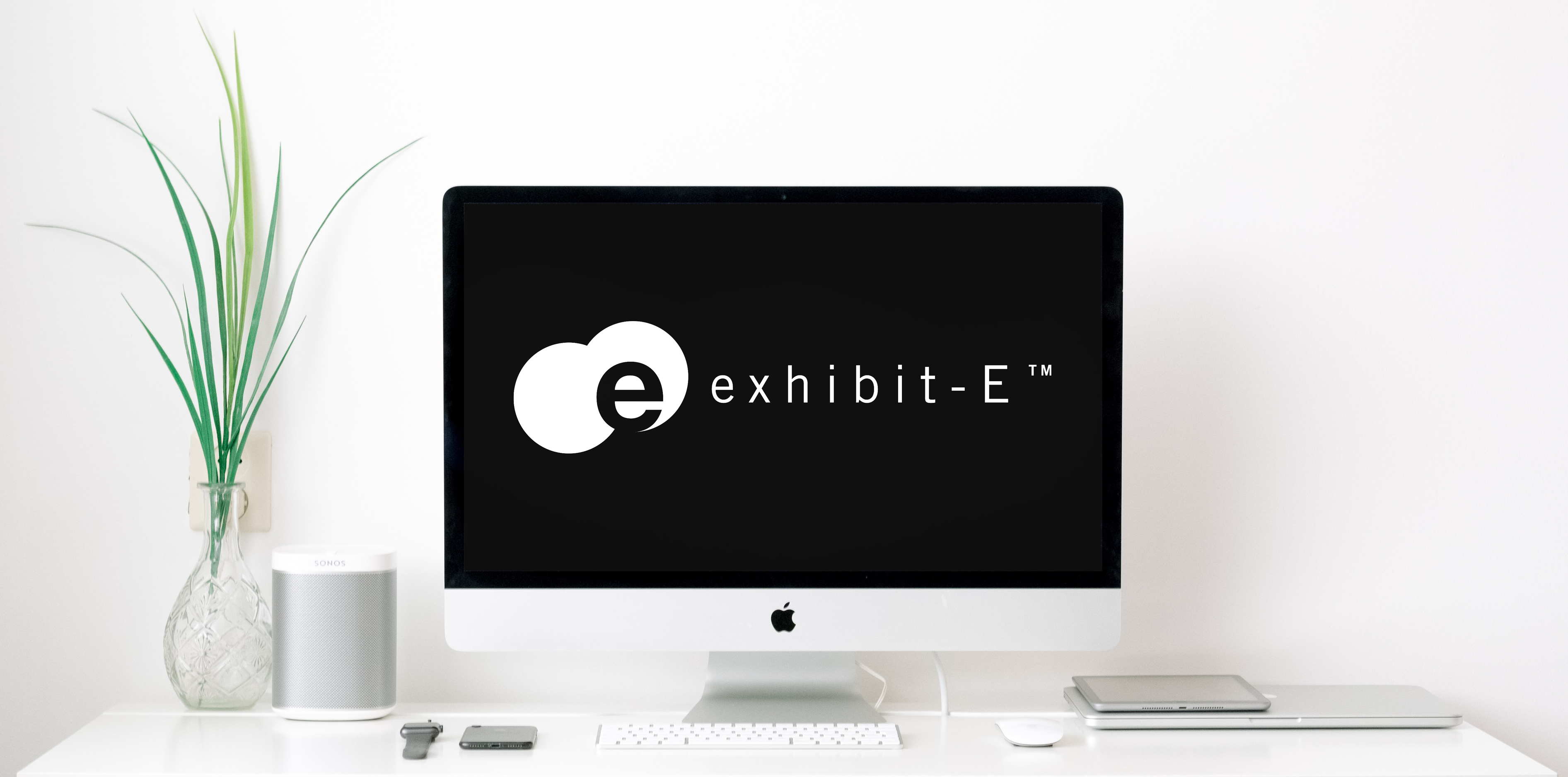 On a white desk there is desktop with a black background with the exhibit-E logo. In addition to the desktop there is a plant in a clear vase and an assortment of various apple technologies.