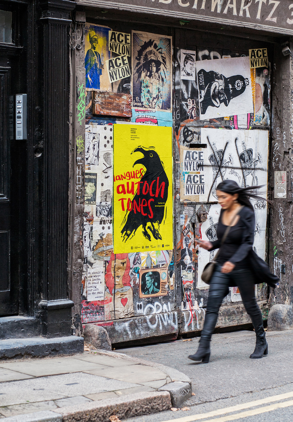 A yellow poster with a black crow and red typography seen somewhere outdoors