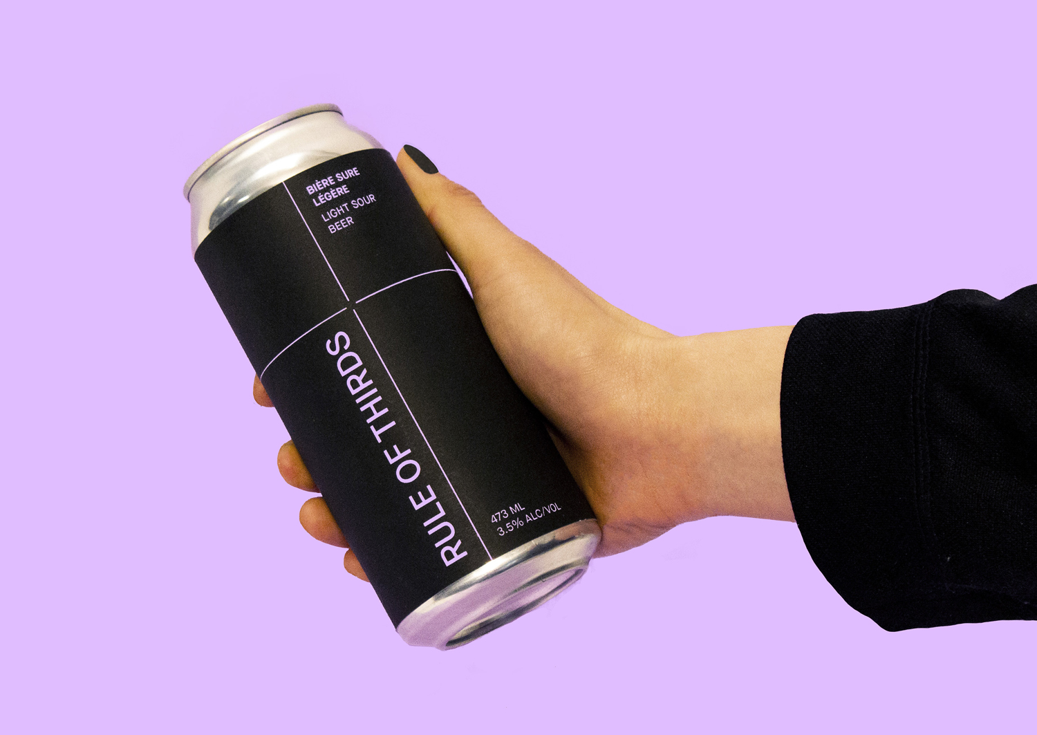 "A hand holding a beer can that reads ""Rule of Thirds"" on a light purple background"