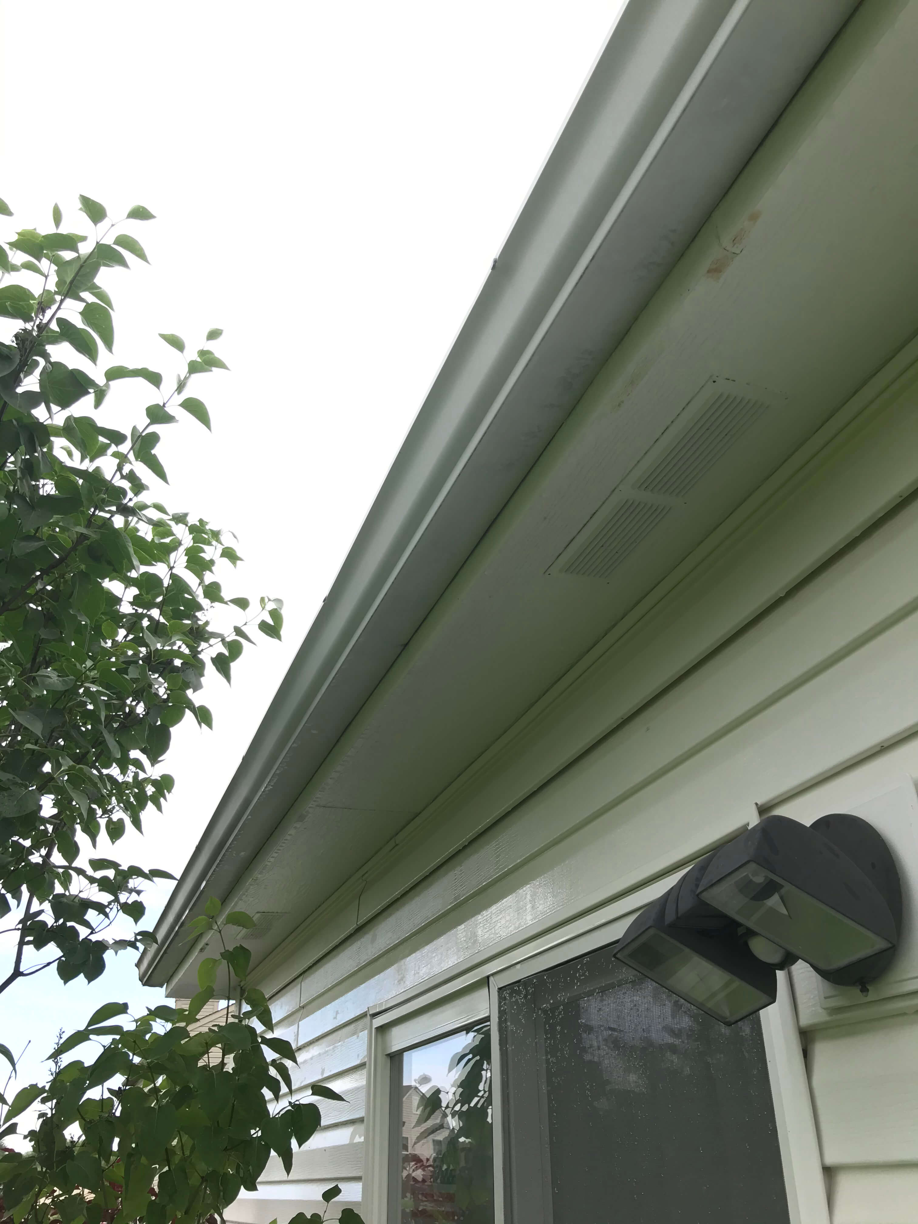 one man and a sprayer gutter cleaning
