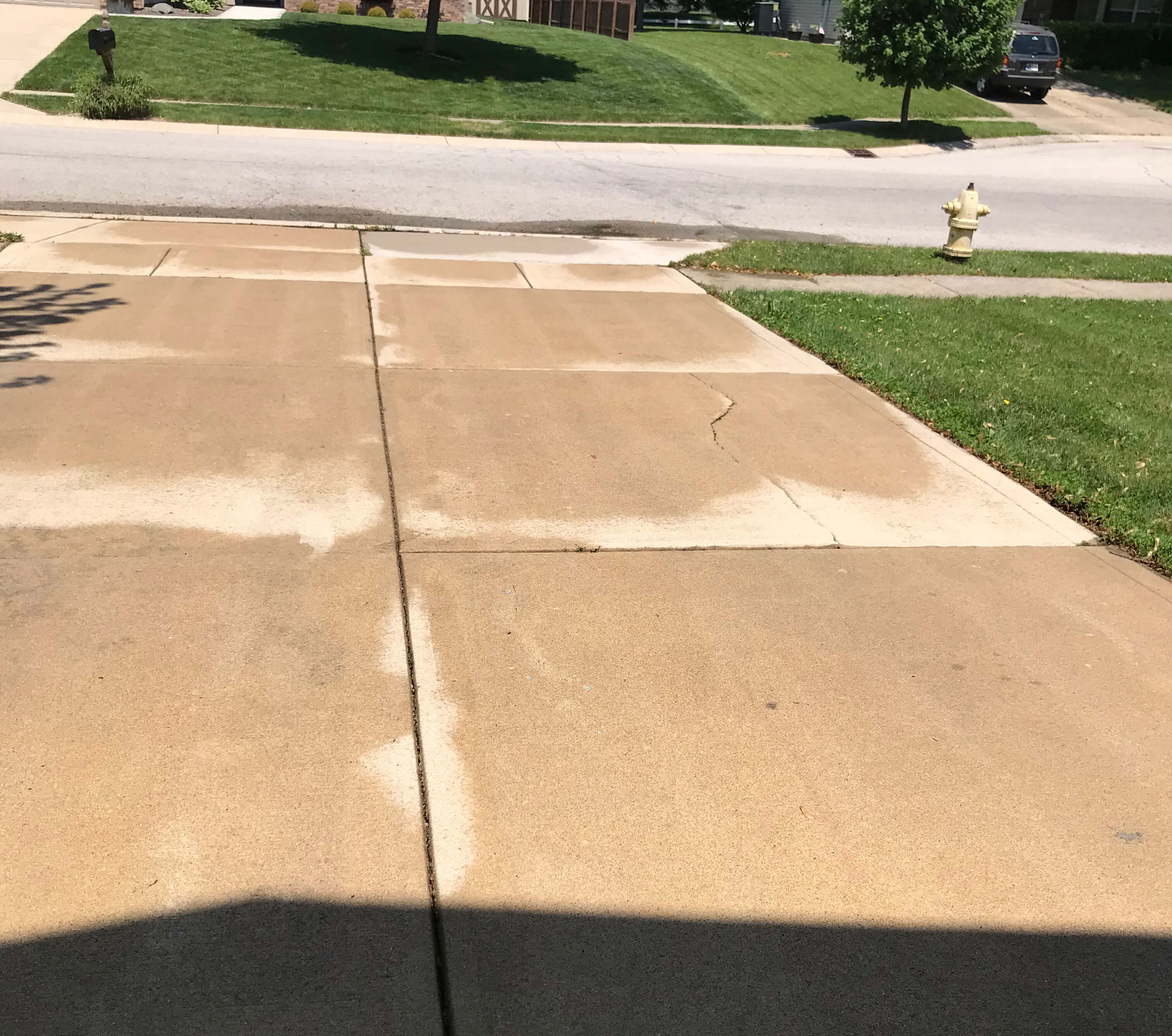 one man and a sprayer driveway cleaning