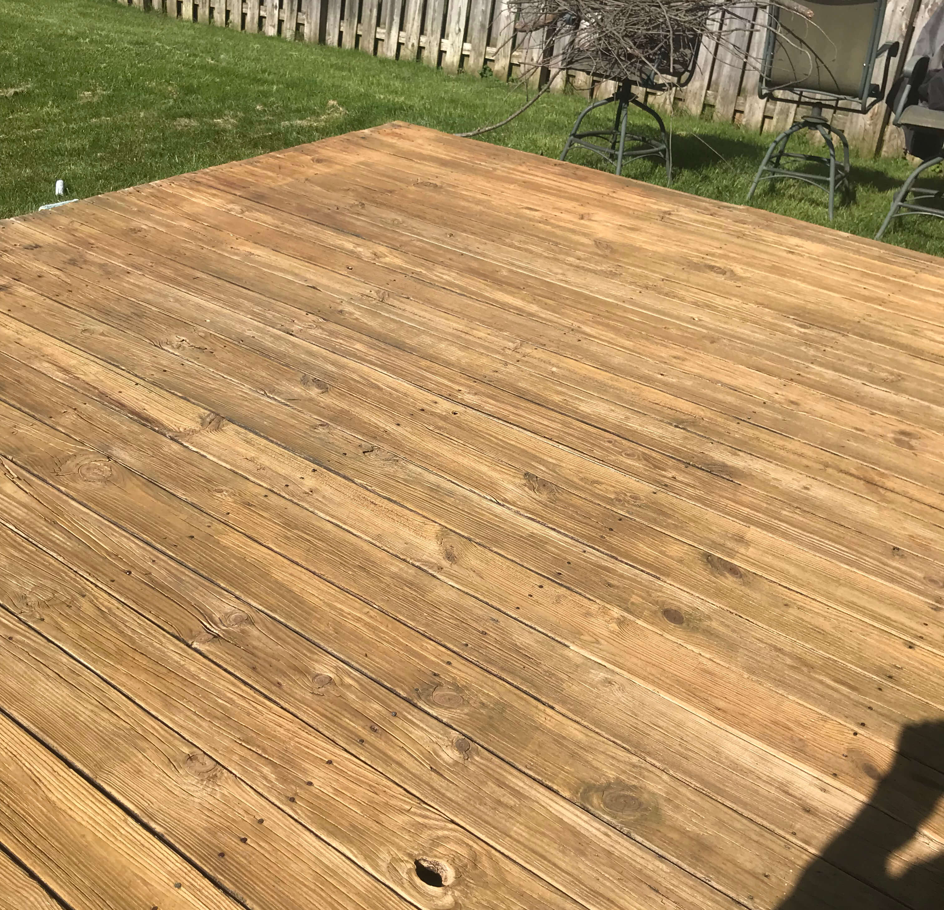 one man and a sprayer power washing and deck staining
