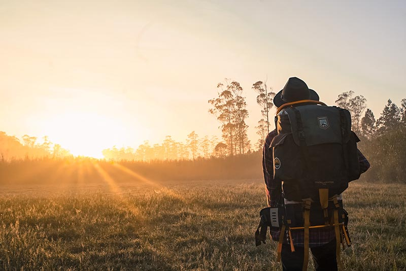 Nomad hiking in an open field at sunrise.