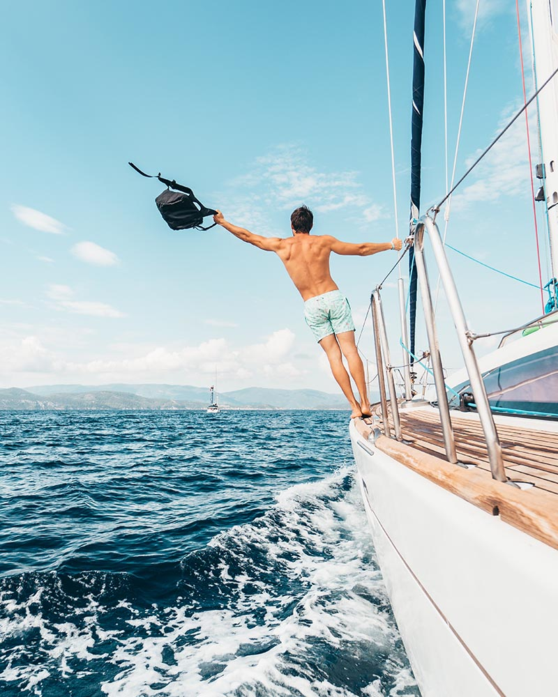 Man standing on the side of a sailboat ready for an adventure.
