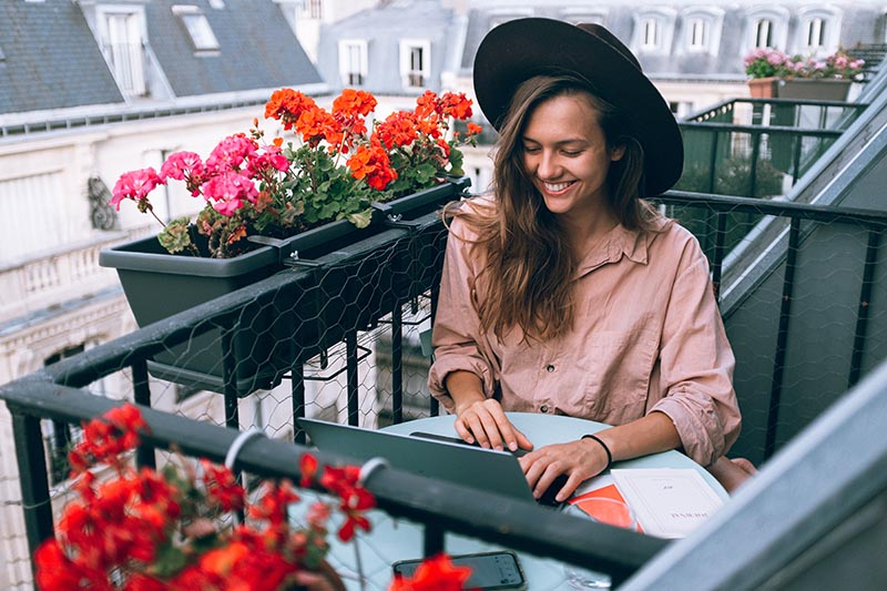 Girl working online on a balcony abroad.
