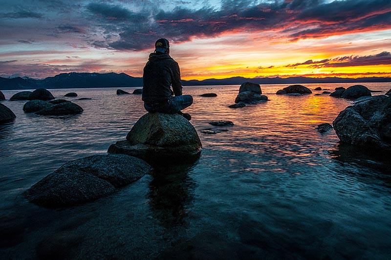 A man sitting on a rock on the coast staring into the sunset.