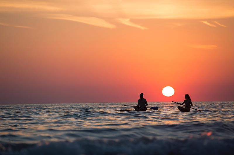 Two people on paddle boards in the ocean at sunset.