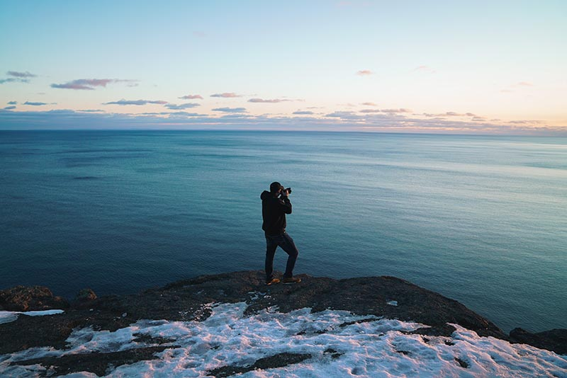 Photographer on the edge of cliff overlooking the ocean taking a photo.