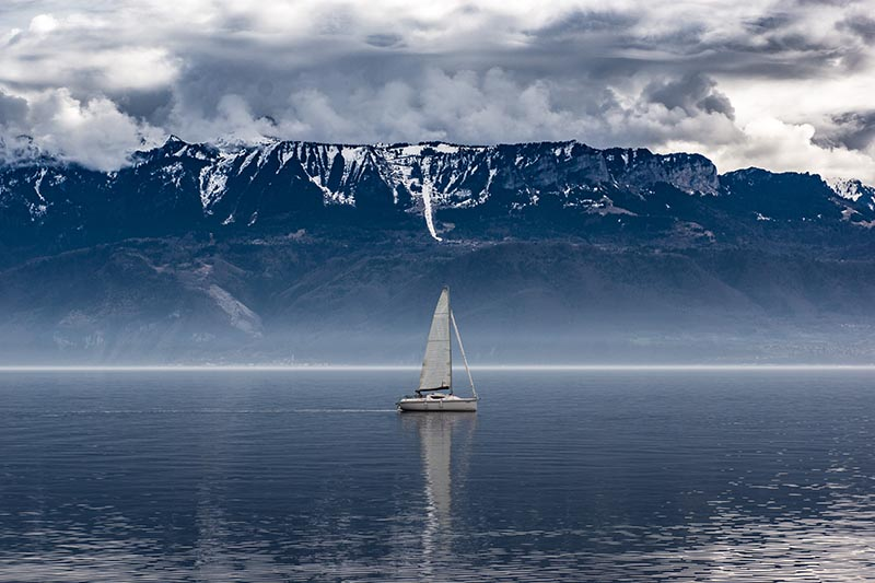 Sailboat on the bay in front of a mountain.